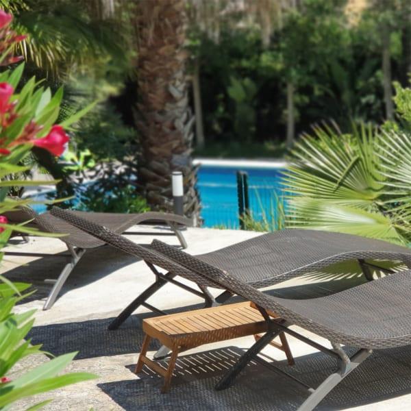 La Casa Dorada pool with chairs and palm trees
